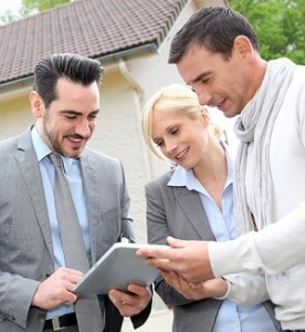 Real estate agent and his buyer clients using a tablet