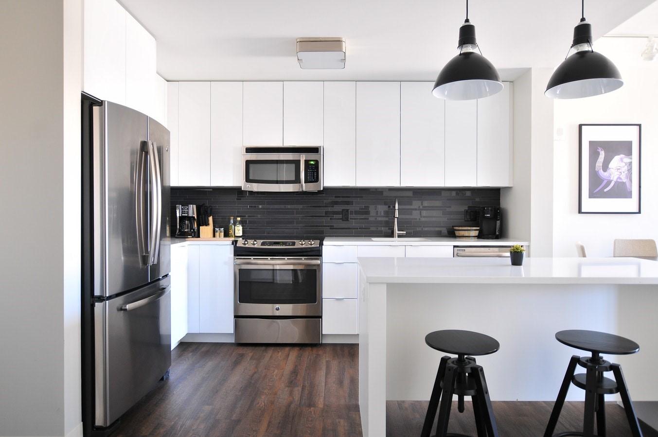 Kitchen with white cupboards, dark hardwood floor and stainless steel applicances