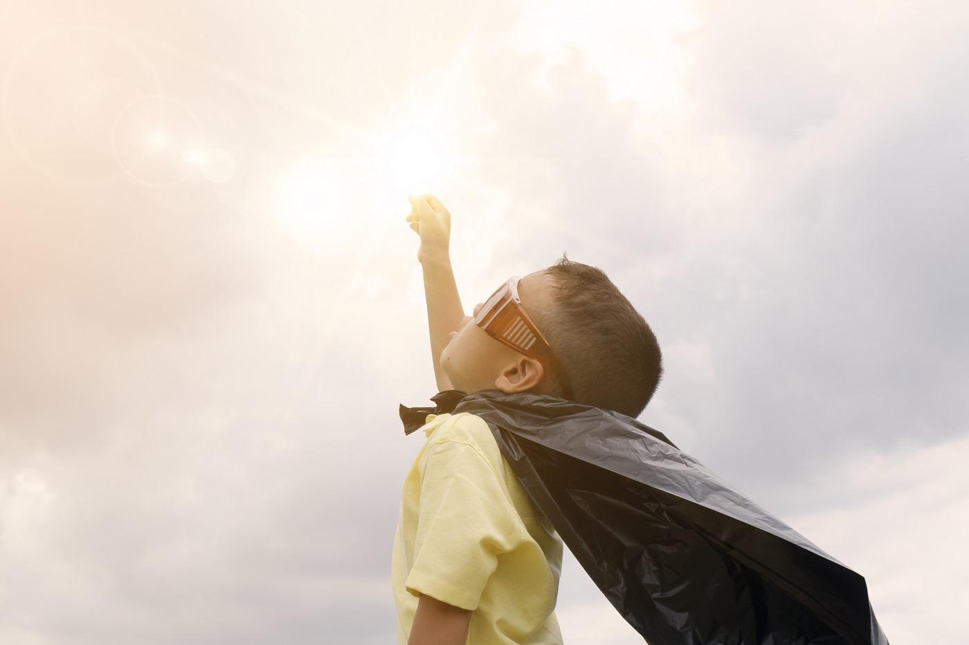 happy kid playing superhero